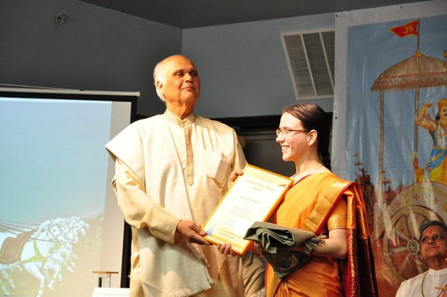 Dr. Doobay awarding the Vishwa Hindu Ratna award to Ms. Kristen Mandziuk of SSRF
