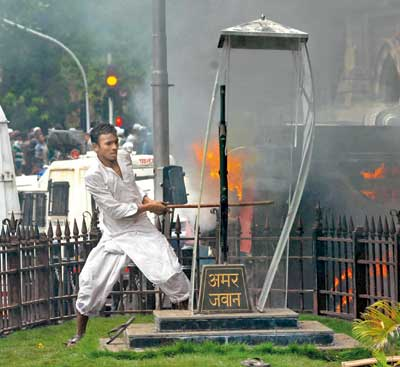 A protester breaks the glass case that encloses the Amar Jawan memorial at CST