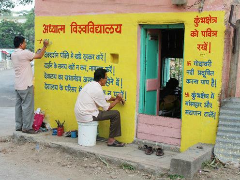 Seekers writing enlightening matter on wall