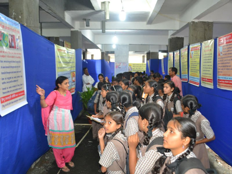 Students being explained the charts at the Exhibition